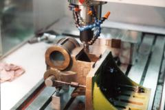 In the Summer of 2003, Bill W., took the rough-milled cylinder saddle halves and machined them for me.  Here, on one of many angle-plate setups, he cuts the bottom of the casting which is bolted to the engine frame.